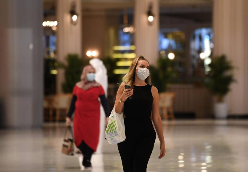 Women wearing masks for protection against the coronavirus, walk in the Mall of Dubai on April 28, 2020, after the shopping centre was reopened as part of moves in the Gulf emirate to ease lockdown restrictions imposed last month to prevent the spread of the COVID-19 illness.  / AFP / Karim SAHIB