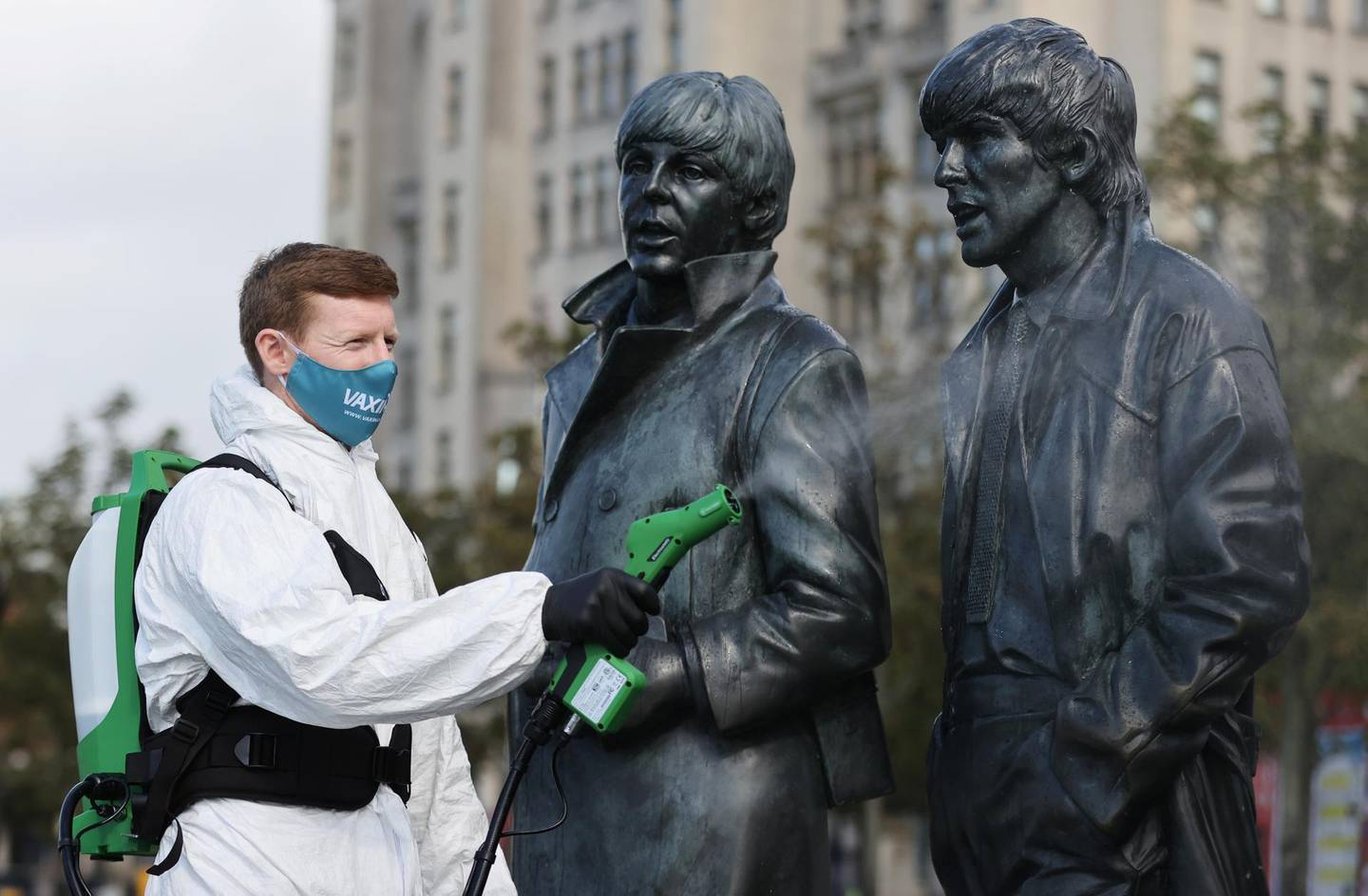 A man disinfects a statue of the Beatles amid the outbreak of the coronavirus disease (COVID-19), in Liverpool, Britain October 1, 2020. REUTERS/Carl Recine