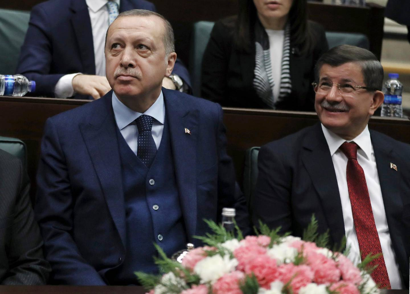 FILE - In this Jan. 30, 2018 file photo, Turkey's President Recep Tayyip Erdogan, left, and former Prime Minister Ahmet Davutoglu look toward the party members at the parliament in Ankara, Turkey. Davutoglu, a former Turkish prime minister, who had served as foreign minister between 2009 and 2014 and later as prime minister until 2016, has established a new political party on Thursday, Dec. 12, 2019, in a move that could dent support for President Recep Tayyip Erdogan's ruling party. (AP Photo/Burhan Ozbilici, File)