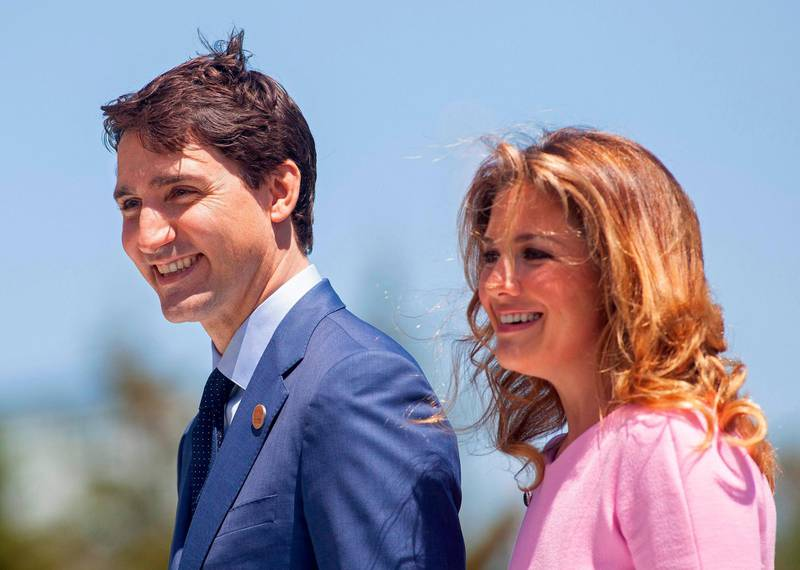 """(FILES) In this file photo taken on June 08, 2018 Prime Minister of Canada Justin Trudeau and his wife Sophie Gregoire Trudeau arrive for a welcome ceremony for G7 leaders on the first day of the summit in La Malbaie, Quebec, Canada. Canadian Prime Minister Justin Trudeau and his wife announced they were self-isolating on March 12, 2020 as she undergoes tests for the new coronavirus after returning from a speaking engagement with """"mild flu-like symptoms."""" Sophie Gregoire-Trudeau's symptoms have subsided since she recently got back from Britain, but as a precaution the prime minister """"will spend the day in briefings, phone calls and virtual meetings from home,"""" according to a statement. / AFP / GEOFF ROBINS"""