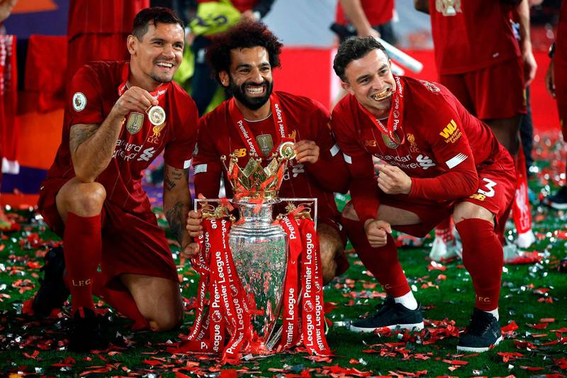 Liverpool's Croatian defender Dejan Lovren (L), Liverpool's Egyptian midfielder Mohamed Salah (C) and Liverpool's Swiss midfielder Xherdan Shaqiri (R) pose with the Premier League trophy during the presentation following the English Premier League football match between Liverpool and Chelsea at Anfield in Liverpool, north west England on July 22, 2020. Liverpool on Wednesday lifted the Premier League trophy at the famous Kop stand at Anfield after their final home game of the season. With no fans able to attend due to the COVID-19 coronavirus pandemic, Liverpool said the idea for the trophy lift was to honour the club's fans, but Liverpool manager Jurgen Klopp urged fans to respect social distancing measures, after thousands gathered around the club's stadium and in the city centre following their coronation as champions last month. - RESTRICTED TO EDITORIAL USE. No use with unauthorized audio, video, data, fixture lists, club/league logos or 'live' services. Online in-match use limited to 120 images. An additional 40 images may be used in extra time. No video emulation. Social media in-match use limited to 120 images. An additional 40 images may be used in extra time. No use in betting publications, games or single club/league/player publications.  / AFP / POOL / PHIL NOBLE / RESTRICTED TO EDITORIAL USE. No use with unauthorized audio, video, data, fixture lists, club/league logos or 'live' services. Online in-match use limited to 120 images. An additional 40 images may be used in extra time. No video emulation. Social media in-match use limited to 120 images. An additional 40 images may be used in extra time. No use in betting publications, games or single club/league/player publications.