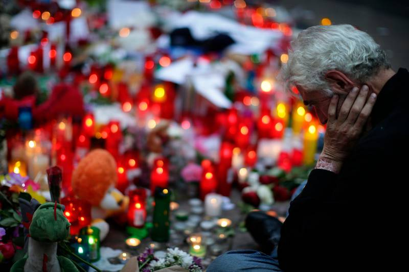 A man looks at flags, messages and candles placed after a van attack that killed at least 13, in central Barcelona, Spain, Saturday, Aug. 19, 2017. Police on Friday shot and killed five people carrying bomb belts who were connected to the Barcelona van attack, as the manhunt intensified for the perpetrators of Europe's latest rampage claimed by the Islamic State group. (AP Photo/Manu Fernandez)