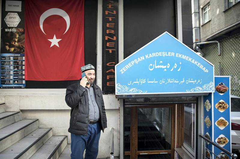 An Uyghur man talks on the phone in front of a Uyghur restaurant.There is huge number of Uyghur community lives in Zeytinburnu district of Istanbul.Thye opened their restaurants,butchers,phone stores around the district.