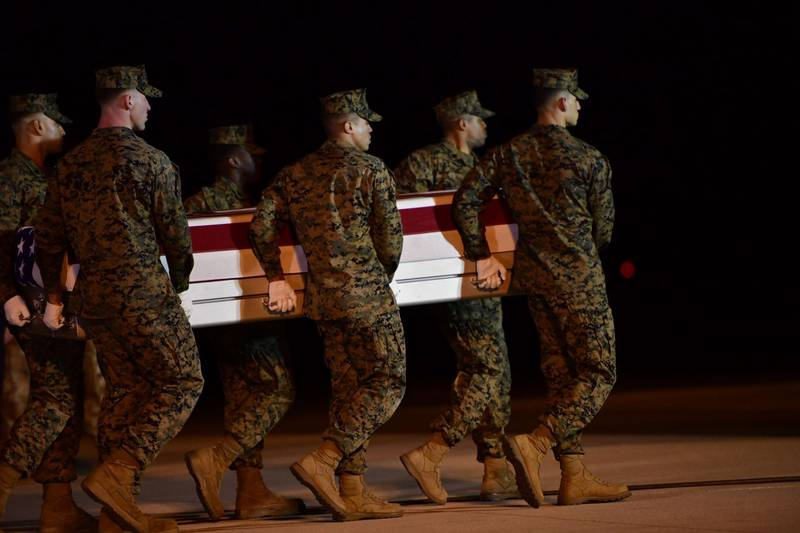 DOVER, DE - MARCH 11: Military personnel carry a transfer case for fallen service member U.S. Marine Gunnery Sgt. Diego D. Pongo, 34, during a dignified transfer at Dover Air Force Base on March 11, 2020 in Dover, Delaware. Pongo and Capt. Moises A. Navas was killed Sunday during a raid on a ISIS complex in Iraq, as part of Operation Inherent Resolve, according to a Department of Defense release.   Mark Makela/Getty Images/AFP == FOR NEWSPAPERS, INTERNET, TELCOS & TELEVISION USE ONLY ==