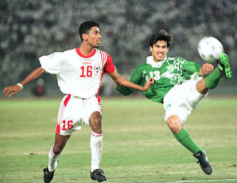 Saudi Arabia forward Hussein Omar (R) shoots the ball away from Emiraty defender Hassan Ahmed (L) during their Asian cup finals in Abu Dhabi stadium, 21 December . (Photo by RAMZI HAIDAR / AFP)
