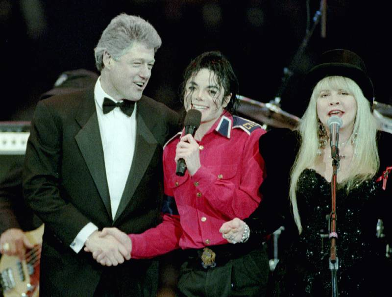 President-elect Bill Clinton (L) shakes hands with singer Michael Jackson as Stevie Nicks of the Fleetwood Mac band sings at the finale of a star-studded gala on the eve of the inauguration at the Capital Center January 19