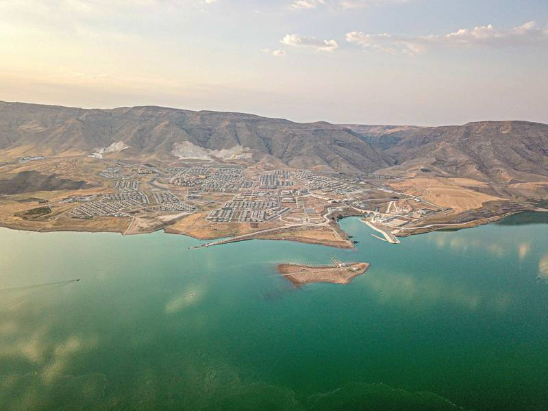 This picture taken on August 6, 2020, shows the Il?su Dam separating the  newly government built Hasankeyf town and the remains of the ancient town of the same name and its archaeological sites which were flooded as part of the Il?su Dam project located along the Tigris River in the Batman Province in southeastern Turkey. - Despite years of protests by residents and activists, the town on the banks of the Tigris River disappeared under water as part of a controversial dam project. To encourage tourism, swimming is allowed and people can enjoy a boat tours. (Photo by BULENT KILIC / AFP)