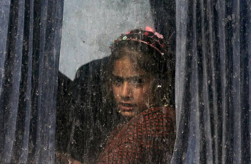 TOPSHOT - An Iraqi girl sits in a bus transporting displaced families from the displaced persons camp in Habbaniyah in Iraq's Anbar province on November 10, 2020. After five years hosting displaced Iraqis, the vast camp was emptied in under 48 hours. The Habbaniyah Tourist Camp, a former luxury resort used to house Iraqis fleeing the Islamic State group, closed this week as part of a sudden government push to shutter dozens of displacement camps by the end of the year.  / AFP / AHMAD AL-RUBAYE