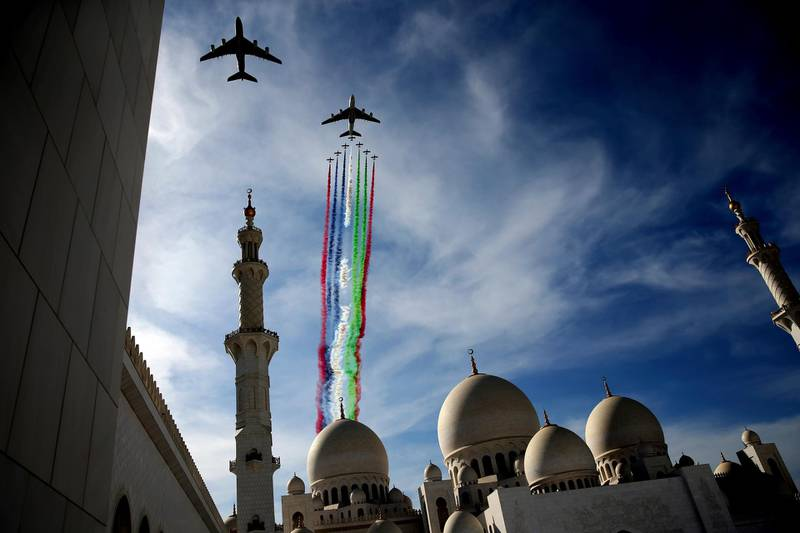 Two Etihad and Emirates planes, followed by the Al Fursan aerobatic team, perform a display show over the Sheikh Zayed Grand Mosque to celebrate the UAE's 47th National Day and the Year of Zayed, in Abu Dhabi, United Arab Emirates, Sunday, Dec. 2, 2018. (AP Photo/Kamran Jebreili)