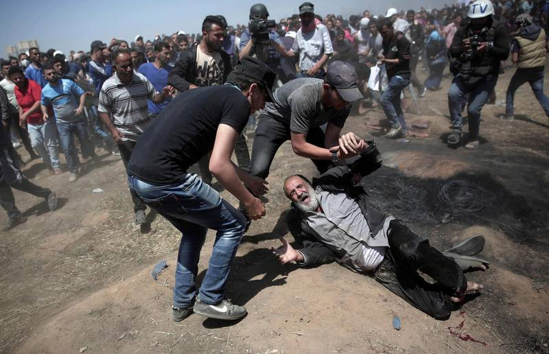 FILE - In this May 14, 2018 file photo, an elderly Palestinian man falls on the ground after being shot by Israeli troops during a deadly protest at the Gaza Strip's border with Israel, east of Khan Younis, Gaza Strip. The modern Middle East has been plagued by ruinous wars: country versus country, civil wars with internecine and sectarian bloodletting, and numerous eruptions centered in the Israeli-Palestinian conflict. But never in the last 70 years have they seemed as interconnected as now with Iran and Saudi Arabia vying for regional control, while Israel also seeks to maintain a military supremacy of its own. (AP Photo/Khalil Hamra, File)