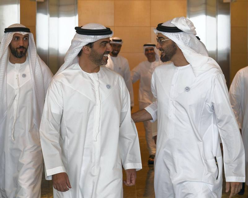 ABU DHABI, UNITED ARAB EMIRATES -  March 07, 2018: HH Sheikh Mohamed bin Zayed Al Nahyan, Crown Prince of Abu Dhabi and Deputy Supreme Commander of the UAE Armed Forces (R), speaks with HH Sheikh Hamed bin Zayed Al Nahyan, Chairman of the Crown Prince Court of Abu Dhabi and Abu Dhabi Executive Council Member (L), prior to a board meeting at the Abu Dhabi Investment Authority (ADIA). Seen with HE Mohamed Mubarak Al Mazrouei, Undersecretary of the Crown Prince Court of Abu Dhabi (back L).  ( Ryan Carter for the Crown Prince Court - Abu Dhabi ) ---