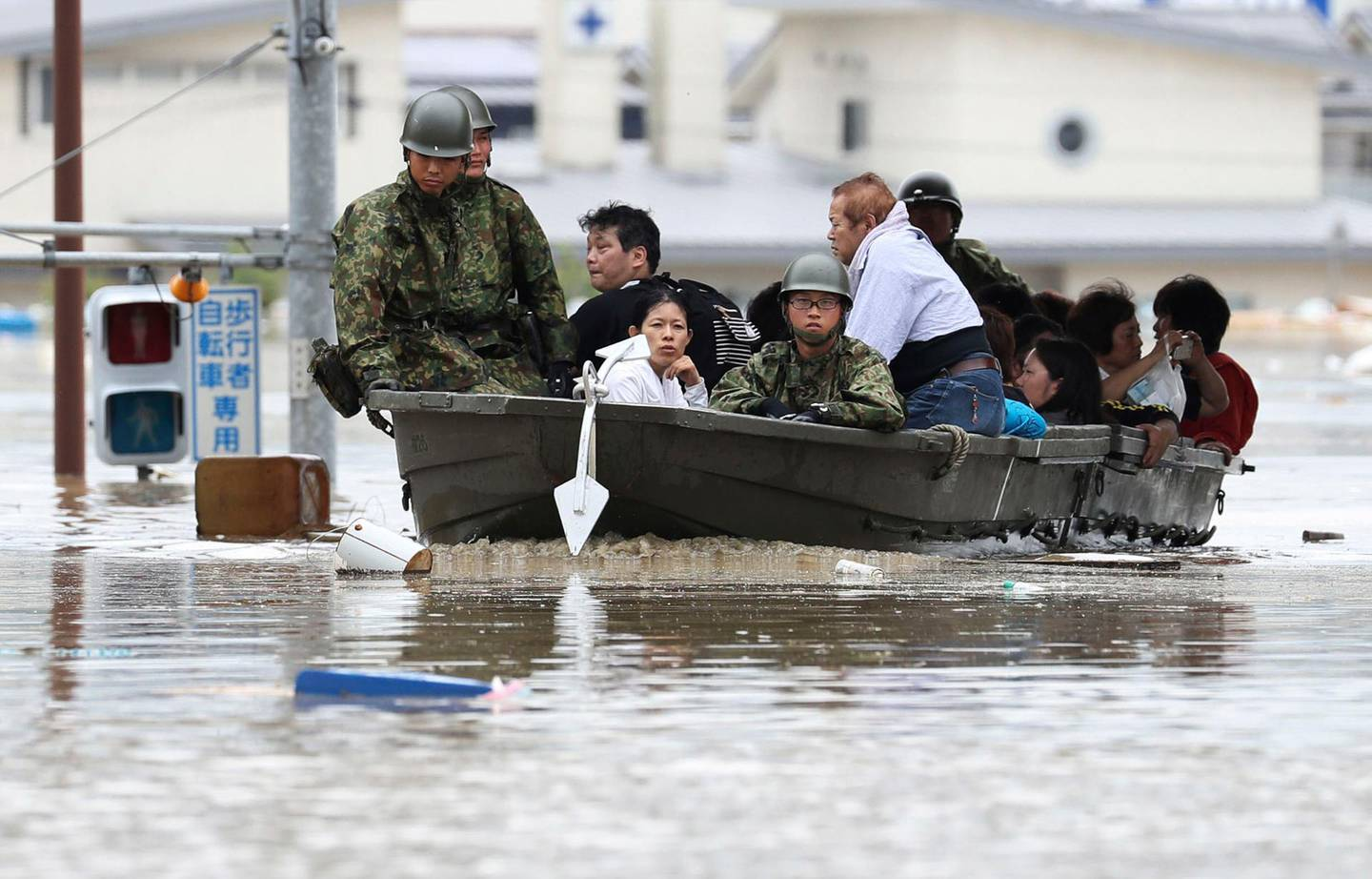 Japan Ground Self-Defense Force members use a boat to evacuate residents from a flooded area caused by heavy rains in Kurashiki, Okayama prefecture, southwestern Japan, Saturday, July 7, 2018. Torrents of rainfall and flooding continued to batter southwestern Japan. (Takumi Sato/Kyodo News via AP)