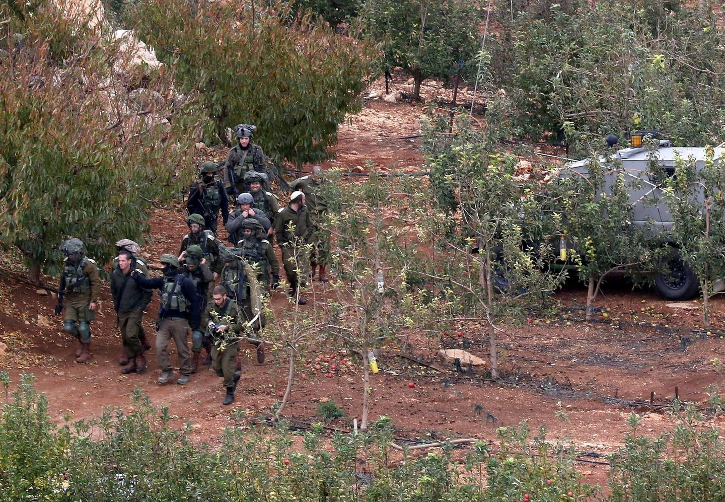 A picture taken on December 5, 2018 from the souther Lebanese village of Kfar Kila shows Israeli soldiers walking near the site of an Israeli excavation site for reported Hezbollah-dug tunnels along the Lebanon-Israel border. Israel had announced on December 4 that it had discovered Hezbollah tunnels infiltrating its territory from Lebanon and launched an operation to destroy them. / AFP / Mahmoud ZAYYAT