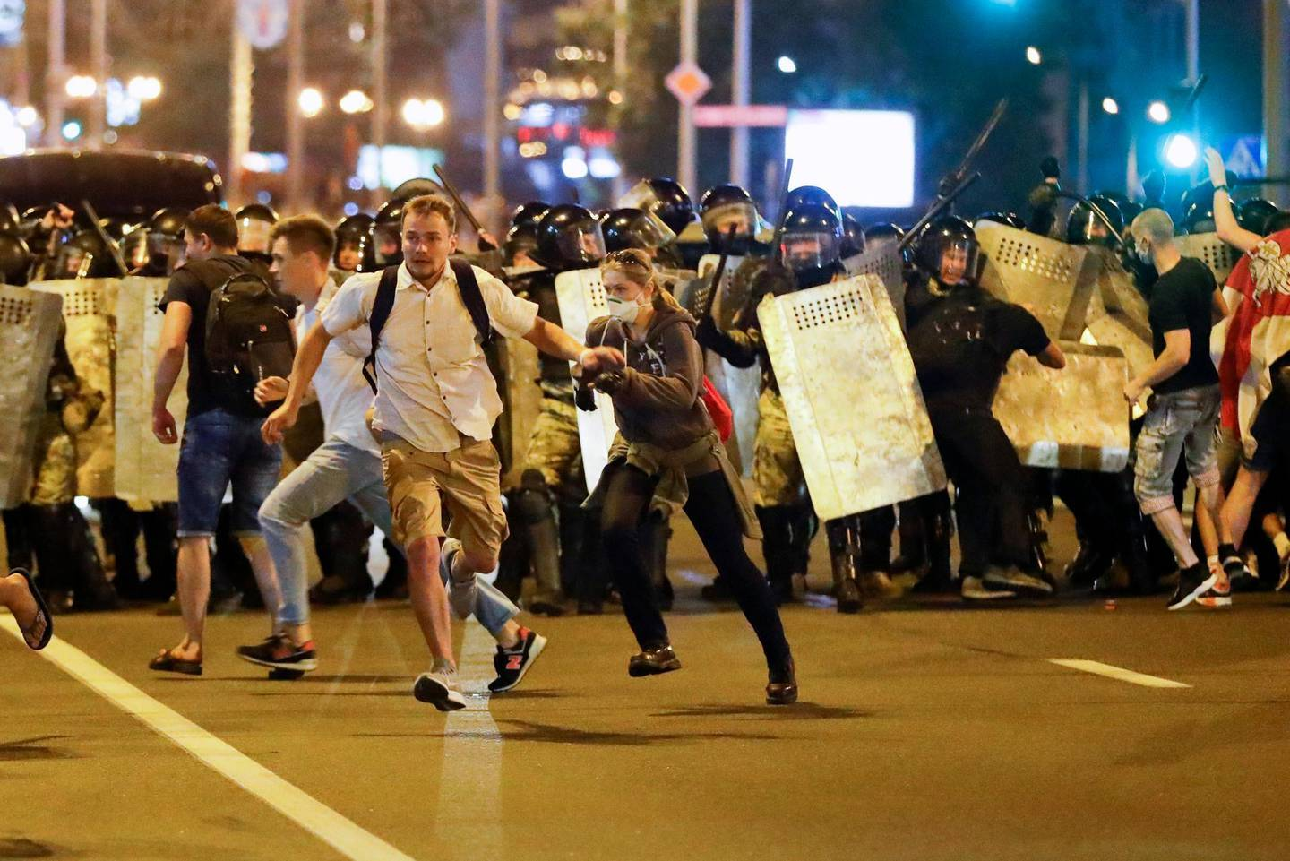 Demonstrators run away from police as they gather to protest against a result of the Belarusian presidential election in Minsk, Belarus, Sunday, Aug. 9, 2020. Police and protesters clashed in Belarus' capital and the major city of Brest on Sunday after the presidential election in which the authoritarian leader who has ruled for a quarter-century sought a sixth term in office. (AP Photo/Sergei Grits)