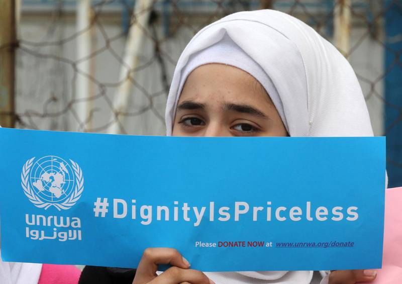 A Palestinian refugee holds a placard at a school belonging to the United Nations Relief and Works Agency for Palestinian Refugees (UNRWA) in the town of Sebline east of the southern Lebanese port of Saida, on March 12, 2018, during a protest against US aid cuts to the organisation.  / AFP PHOTO / Mahmoud ZAYYAT