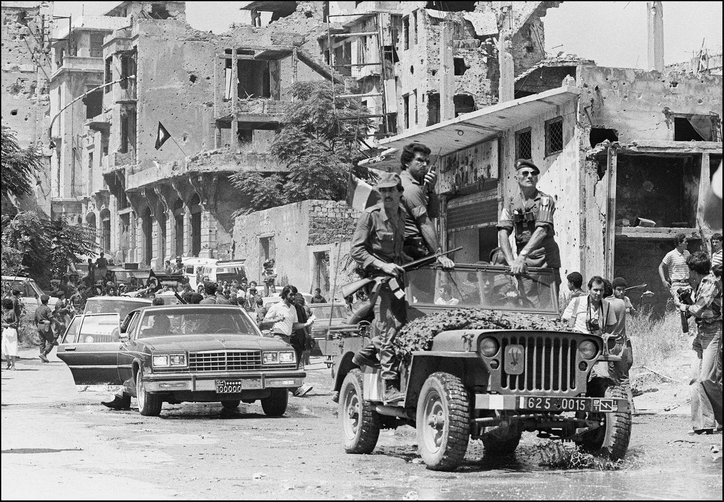 A French paratrooper officer atop a French military jeep (wearing sun glasses) and Palestinian fighters precedes the motorcade of Palestine Liberation Organisation (PLO) chairman Yasser Arafat shown in a picture dated 30 August 1982 in Beirut, surrounded by heavy security as he leaves Israeli-occupied Beirut for Tunis.  EDS NOTE: B/W only. (Photo by Dominique FAGET / AFP)