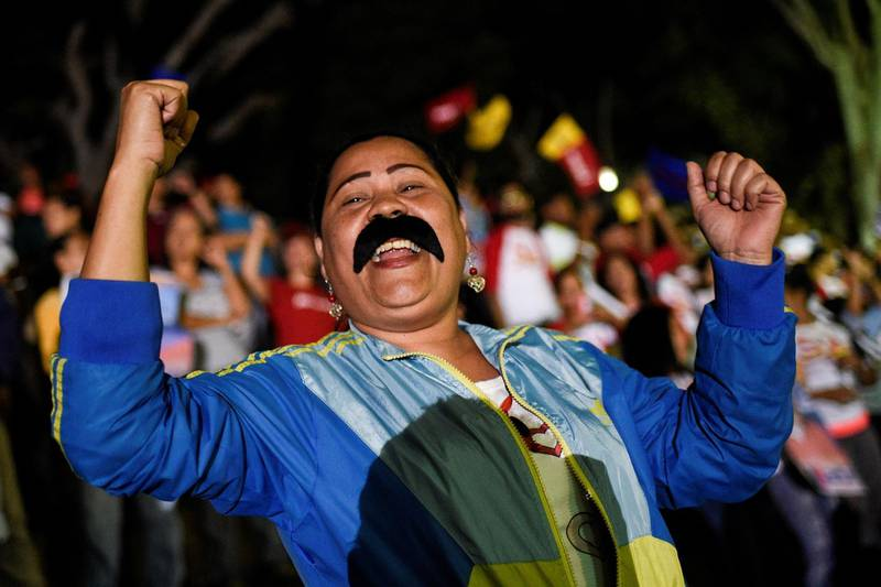 Supporters of the Venezuelan President Nicolas Maduro celebrate after the National Electoral Council (CNE) announced the results of the voting on election day in Venezuela, on May 20, 2018 in Caracas.  President Nicolas Maduro was declared winner of Venezuela's election Sunday in a poll rejected as invalid by his rivals, who called for fresh elections to be held later this year. With more than 90 percent of the votes counted, Maduro had 67.7 percent of the vote, with his main rival Henri Falcon taking 21.2 percent, the National Election Council chief Tibisay Lucena announced. / AFP / Federico PARRA