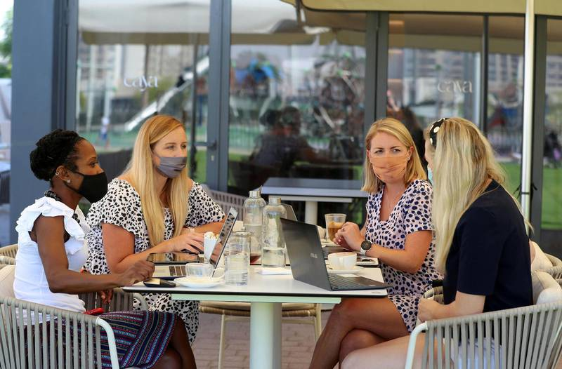 Dubai, United Arab Emirates - Reporter: Patrick Ryan. News. Teams of people are meeting to work remotely together in the same venues that are not offices. Jen Crowther (2nd R), Catherine Broad (R), Natalie Waugh and Lauren Savill (2nd L) work at a restaurant in Town Square. Wednesday, April 7th, 2021. Dubai. Chris Whiteoak / The National