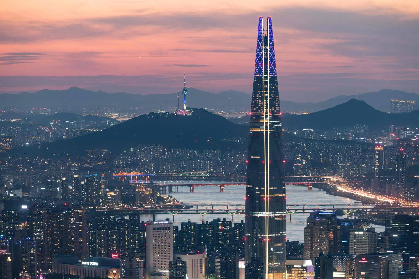"""(FILES) A file photo taken on May 19, 2018 shows a general view of the Lotte tower (front C) and Namsan tower (rear C) amid the Seoul city skyline and Han river during sunset.  French """"Spiderman"""" Alain Robert, who holds a world record for urban climbing, surrendered June 6, 2018 to a """"cat and mouse"""" chase with security as he scaled a 123-story skyscraper in Seoul to celebrate the recent peace-making efforts between the two Koreas.  -   / AFP / Ed JONES"""