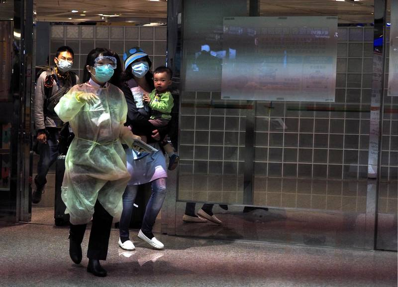 epa08315931 A health worker wearing a protective gown (C) takes a woman and her child (R) to be tested for coronavirus Covid-19 as they arrive at Taoyuan International Airport in Taoyuan, northern Taiwan, 23 March 2020. On 23 March, Taiwan reported 26 new coronavirus Covid-19 infection cases, pushing the total to 195. Of the 26 cases, 25 are 'imported cases.'  EPA/DAVID CHANG