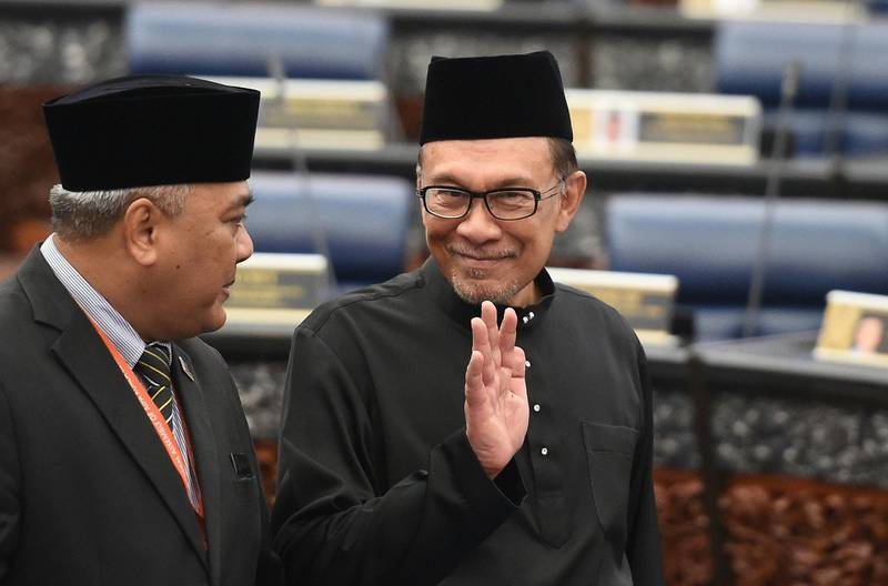 Malaysia's People's Justice Party president and leader of the Pakatan Harapan coalition Anwar Ibrahim (R) waves before taking an oath as a member of the parliament during a swearing-in ceremony at the Parliament House in Kuala Lumpur on October 15, 2018. / AFP / Mohd RASFAN