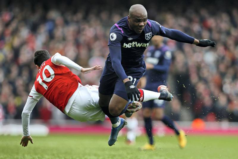 Arsenal's German midfielder Mesut Ozil (L) vies with West Ham United's Italian defender Angelo Ogbonna (R) during the English Premier League football match between Arsenal and West Ham at the Emirates Stadium in London on March 7, 2020. (Photo by Ian KINGTON / AFP) / RESTRICTED TO EDITORIAL USE. No use with unauthorized audio, video, data, fixture lists, club/league logos or 'live' services. Online in-match use limited to 120 images. An additional 40 images may be used in extra time. No video emulation. Social media in-match use limited to 120 images. An additional 40 images may be used in extra time. No use in betting publications, games or single club/league/player publications. /