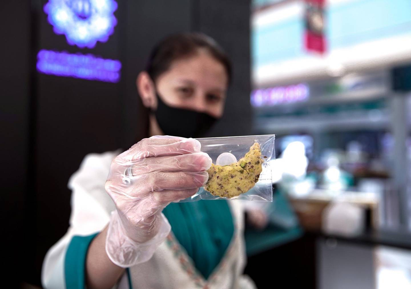 Abu Dhabi, United Arab Emirates, May 18, 2020.    A Moreish Sweets saleslady with some Ramadan sweets at the Al Raha Mall reopening during the Covid-19 pandemic.Victor Besa / The NationalSection:  NAReporter: