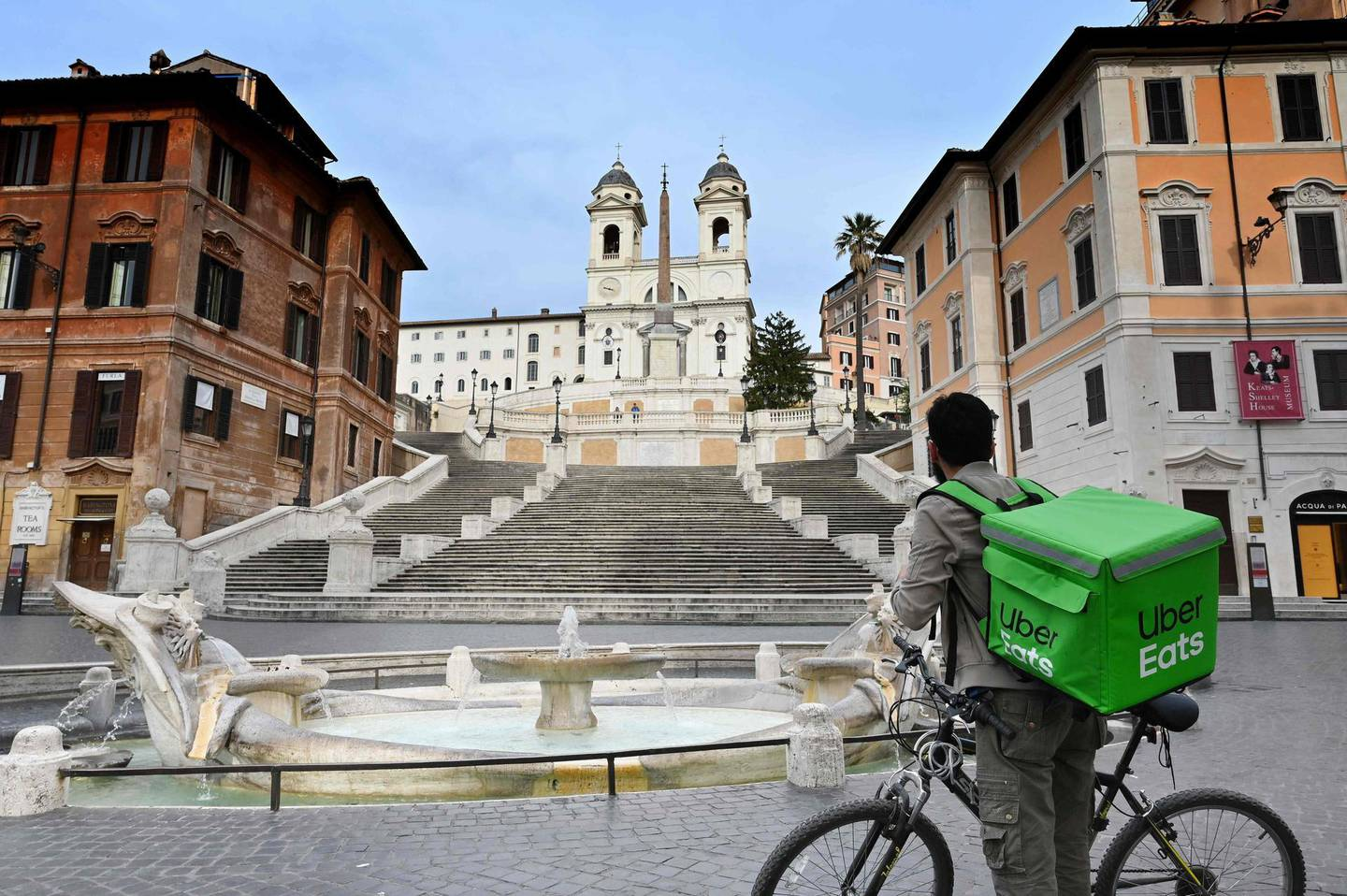 An Uber Eats delivery man stands by hte Spanish Steps at a deserted Piazza di Spagna in central Rome on March 12, 2020, as Italy shut all stores except for pharmacies and food shops in a desperate bid to halt the spread of a coronavirus. / AFP / Alberto PIZZOLI