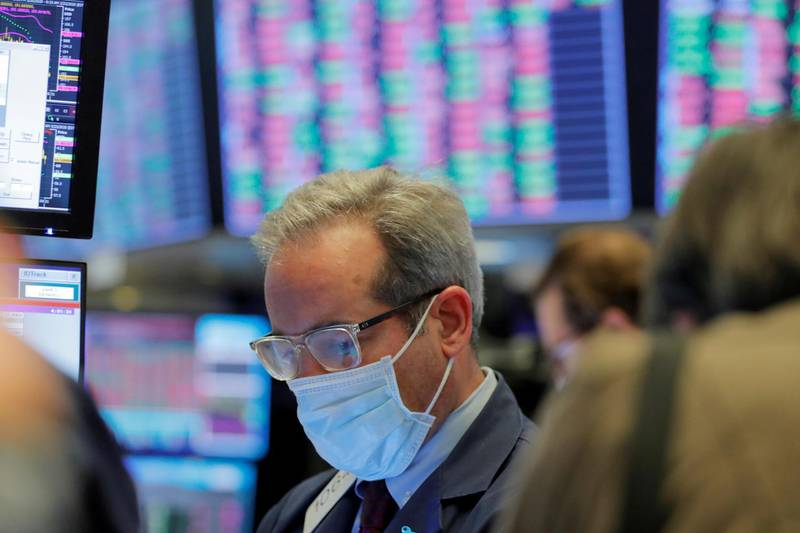 FILE PHOTO: A trader wears a mask as he works on the floor of the New York Stock Exchange (NYSE) as the building prepares to close indefinitely due to the coronavirus disease (COVID-19) outbreak in New York, U.S., March 20, 2020.  REUTERS/Lucas Jackson/File Photo