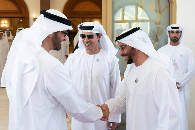 ABU DHABI, UNITED ARAB EMIRATES - August 21, 2018: HH Sheikh Mohamed bin Zayed Al Nahyan Crown Prince of Abu Dhabi Deputy Supreme Commander of the UAE Armed Forces (L) bids farewell to HH Sheikh Hamdan bin Zayed Al Nahyan, Ruler's Representative in Al Dhafra Region (R), at the end of an Eid Al Adha reception at Mushrif Palace. Seen with HH Sheikh Hazza bin Zayed Al Nahyan, Vice Chairman of the Abu Dhabi Executive Council (C).    ( Hamad Al Kaabi / Crown Prince Court - Abu Dhabi ) ---