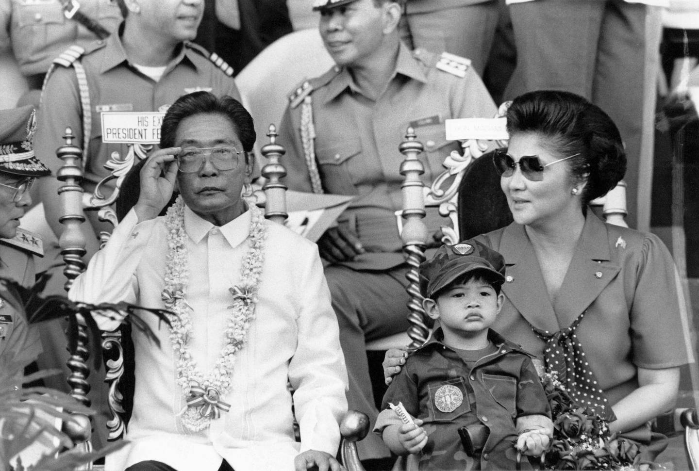(FILES) This file photo taken on November 15, 1985 shows then Philippine president Ferdinand Marcos (L) and his wife Imelda (R) appearing before some 35,000 college students undergoing a two-year compulsory military training in Manila. The Philippine government has lost a decades-old legal effort to seize a multi-million-dollar chunk of Ferdinand Marcos' estate, a special anti-graft court said October 25, 2019, scolding prosecutors for failing to produce admissible evidence. -   / AFP / Romeo GACAD