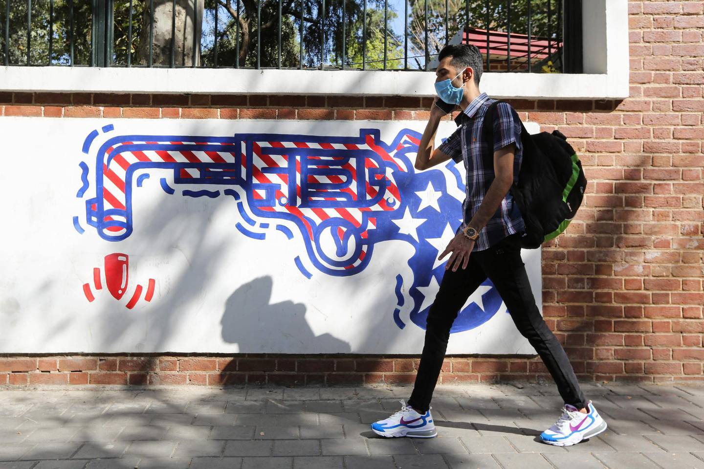"""A man, wearing a protective mask amid the COVID-19 pandemic, walks past a mural painted on the outer walls of the former US embassy in the Iranian capital Tehran on September 20, 2020.   Iran called on the rest of the world to unite against the United States, after Washington unilaterally declared UN sanctions against the Islamic republic were back in force. Washington has said it will """"impose consequences"""" on any country not complying with the sanctions, although the US is one of the only nations that believes they are in force.  / AFP / ATTA KENARE"""
