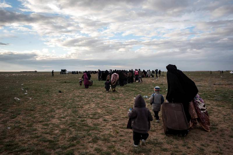 Families walk to be screened by Syrian Democratic Forces after fleeing from the last pocket of ISIS territory outside Baghouz,  Syria, 28 February 2019. Campbell MacDiarmid