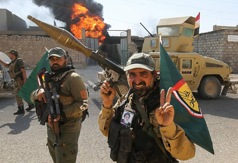 Fighters of Hashed Al-Shaabi (Popular Mobilization units) flash the victory gesture as they advance through a street in the town of Tal Afar, west of Mosul, after the Iraqi government announced the launch of the operation to retake it from Islamic State (IS) group control, on August 26, 2017. (Photo by AHMAD AL-RUBAYE / AFP)