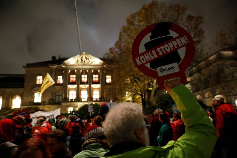 """A protester holds a placard reading """"stop coal"""" during a rally in front of the building of the German Parliamentarian Society that houses the exploratory talks of members of potential coalition parties to form a new government on November 16, 2017 in Berlin. / AFP PHOTO / Odd ANDERSEN"""