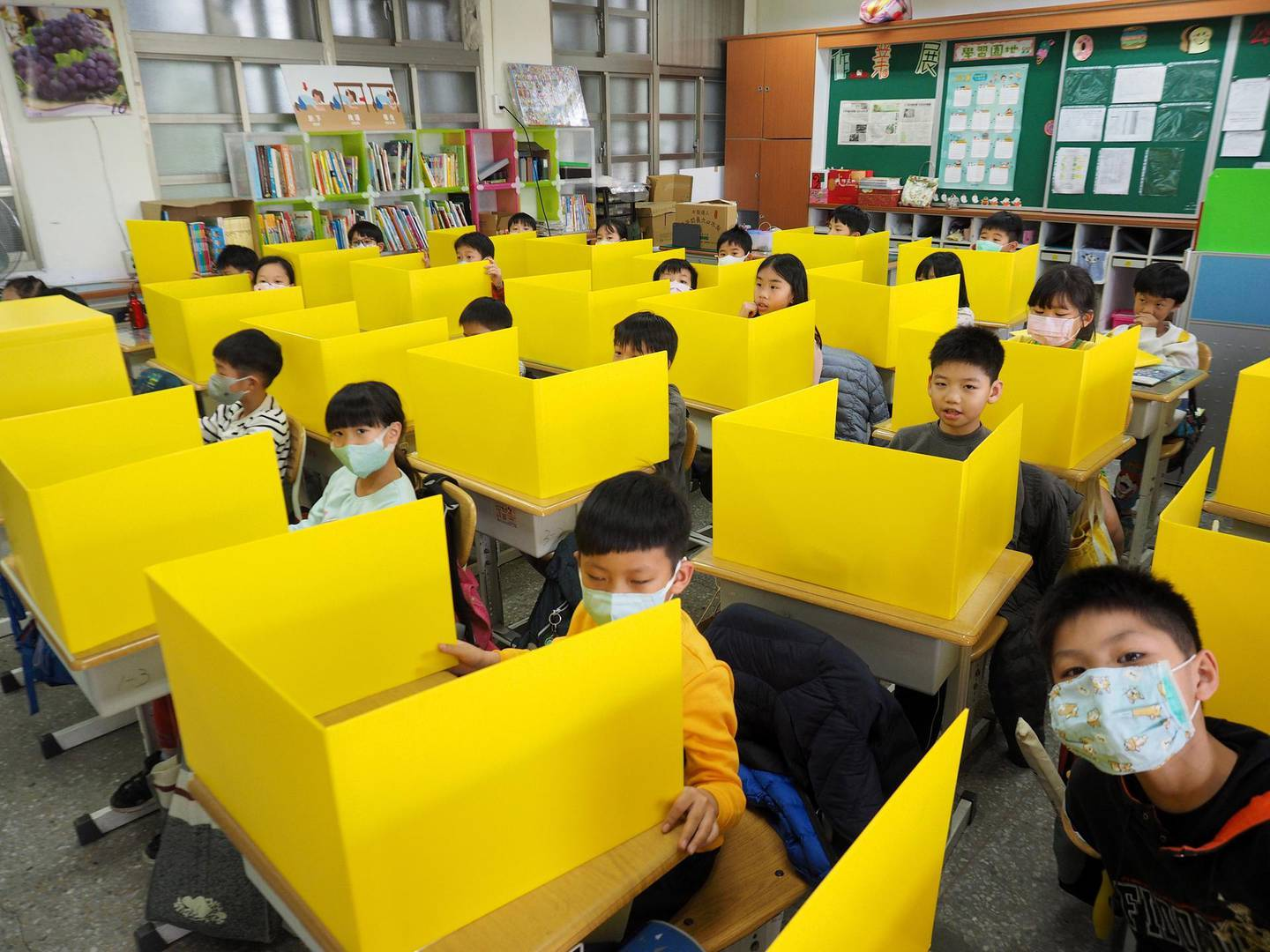 epa08267030 Pupils, with some of them wearing face masks, sit behind partition boards as they attend class at Dajia Elemental School in Taipei, Taiwan, 03 March 2020. The school prepared the boards, made with PP Corrugated Board, to prevent infection of Covid-19 coronavirus by saliva when pupils talk, cough, sneeze or eat lunch in the classroom.  EPA/DAVID CHANG