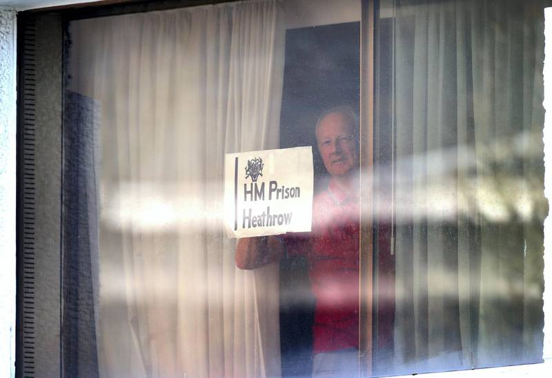 """A man holds a sign against a window at the Renaissance London Heathrow Hotel, near Heathrow Airport, London, a Government-designated quarantine hotel being used for travellers to stay during a 10-day quarantine after returning to England from one of 33 """"red list"""" countries. Picture date: Wednesday February 24, 2021. (Photo by Yui Mok/PA Images via Getty Images)"""