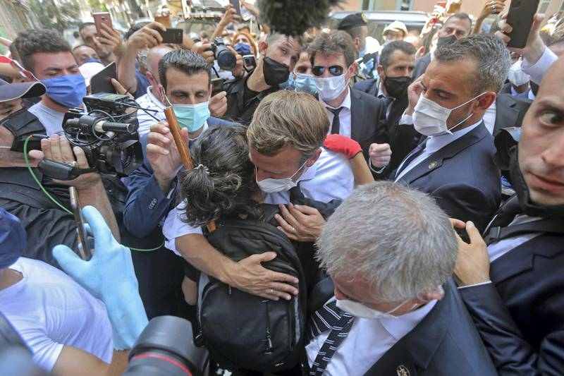 A Lebanese youth hugs French President Emmanuel Macron during a visit to the Gemmayzeh neighbourhood, which has suffered extensive damage due to a massive explosion in the Lebanese capital, on August 6, 2020. French President Emmanuel Macron visited shell-shocked Beirut, pledging support and urging change after a massive explosion devastated the Lebanese capital in a disaster that has sparked grief and fury. / AFP / -