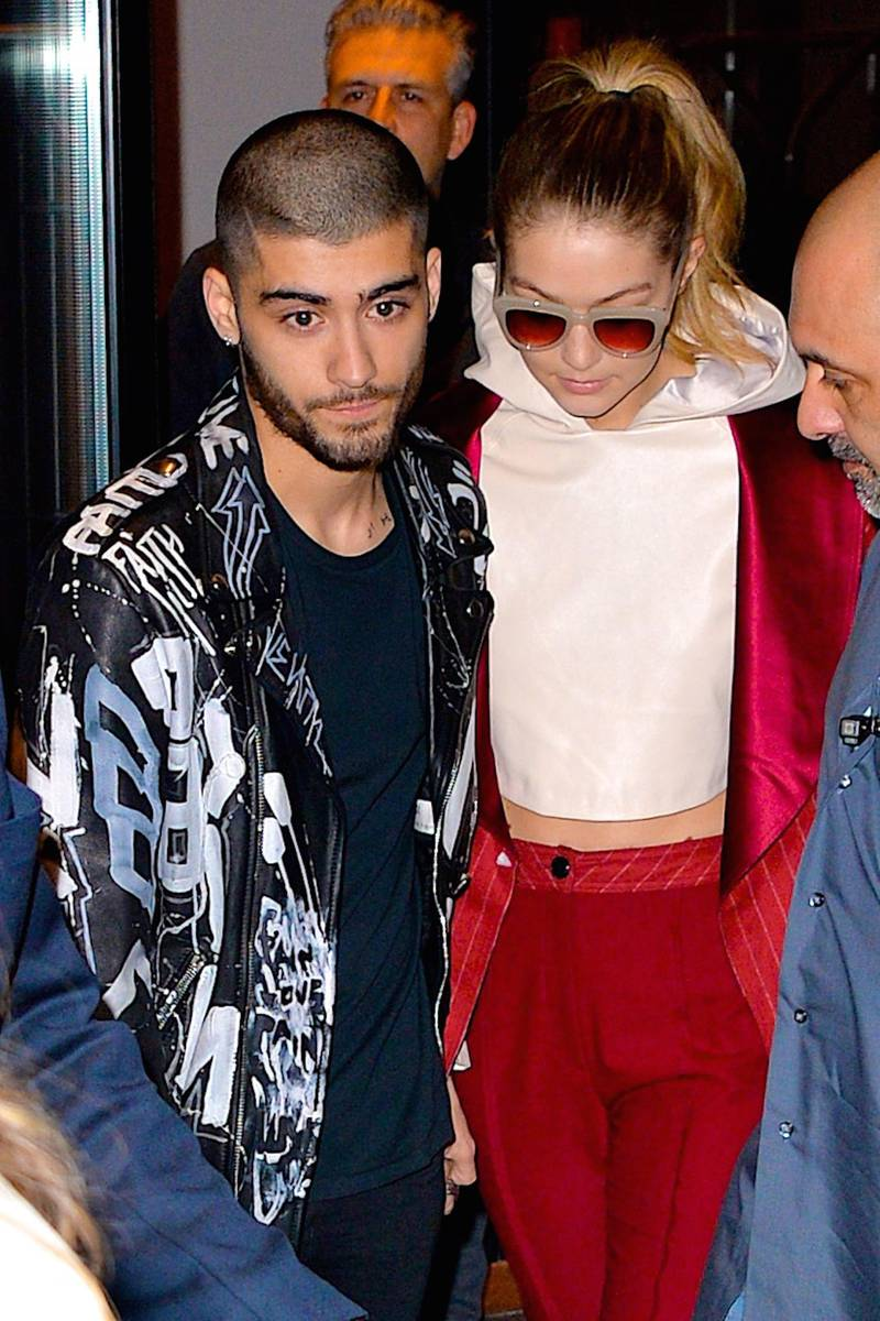 NEW YORK, NY - MARCH 25:  Zayn Malik and girlfriend supermodel Gigi Hadid help a fan that fainted after seeing the couple leaving their East Village apartment on March 25, 2016 in New York City.  (Photo by Robert Kamau/GC Images)