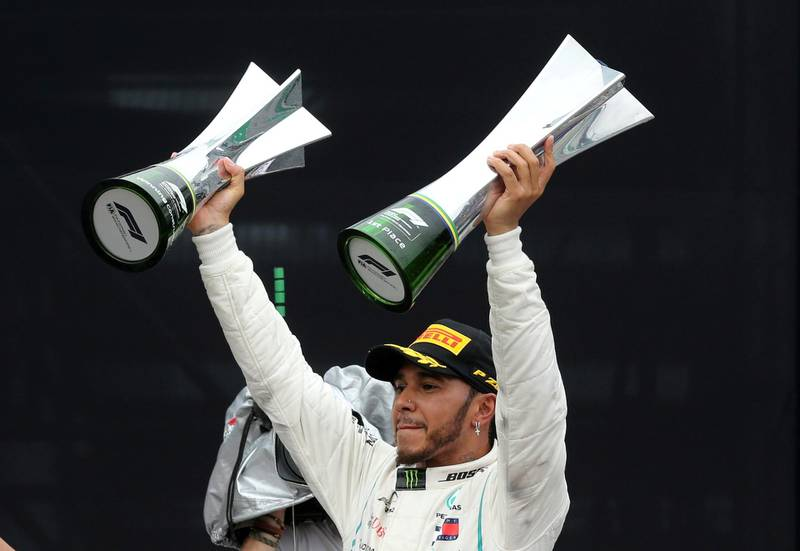 FILE PHOTO: Formula One F1 - Brazilian Grand Prix - Autodromo Jose Carlos Pace, Interlagos, Sao Paulo, Brazil - November 11, 2018  Mercedes' Lewis Hamilton celebrates after winning the race with the constructors championship trophy and the race trophy  REUTERS/Paulo Whitaker/File Photo