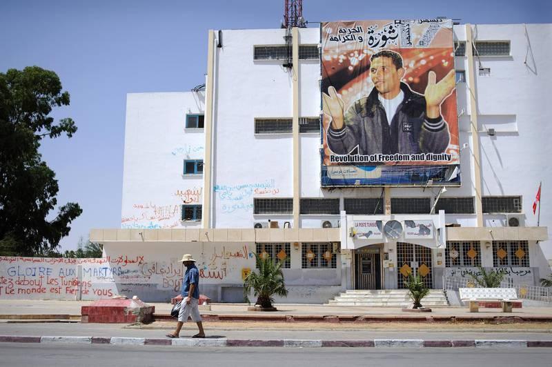 A man walks past revolutionary graffiti and a poster celebrating the martyr Mohammed Bouazizi in Sidi Bouzid, Tunisia. Photo: Lindsay Mackenzie for The National.
