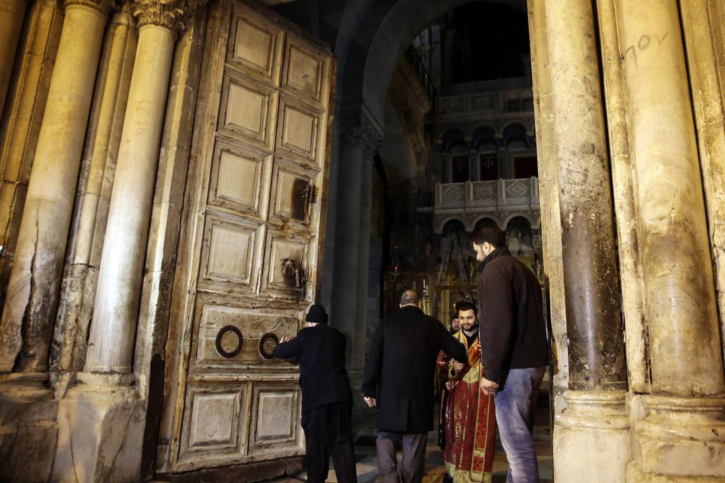 Christian clerics open the doors of the Church of the Holy Sepulchre, traditionally believed by many Christians to be the site of the crucifixion and burial of Jesus Christ, in Jerusalem, Wednesday, Feb. 28, 2018. Christian leaders said Tuesday that they will reopen the Church of the Holy Sepulchre in Jerusalem after Israeli officials suspended a plan to impose taxes on church properties in the holy city. (AP Photo/Mahmoud Illean)