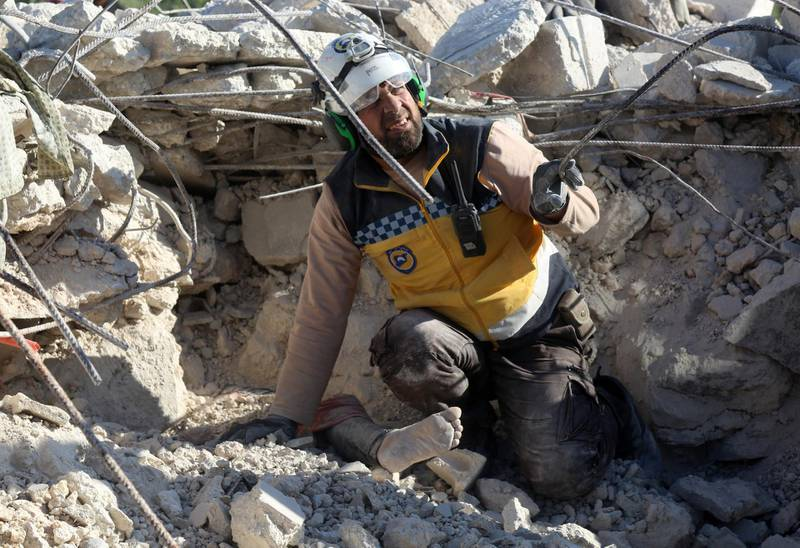 A member of the Syrian Civil Defence (White Helmets) reacts as he prepares to help remove the body of a woman burried under the rubble of a building, who was reportedly killed during shelling by government and allied forces in the village of Rakaya Sijneh, in the southern countryside of the rebel-held Idlib province on May 4,2019.  Attacks by Syrian regime forces and their Russian allies killed 12 civilians in the country's northwest yesterday in the latest violation of an eight-month-old truce, a war monitor said. / AFP / -