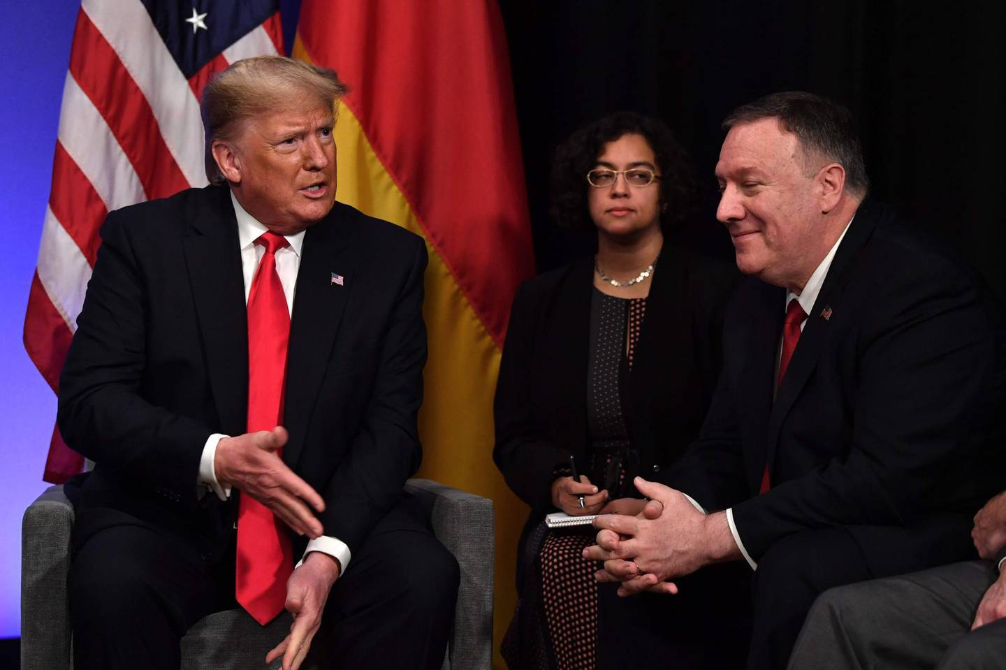 US President Donald Trump (L) speaks to US Secretary of State Mike Pompeo after a bilateral meeting with German Chancellor Angela Merkel on the sidelines of the NATO summit at the Grove hotel in Watford, northeast of London on December 4, 2019. / AFP / Nicholas Kamm