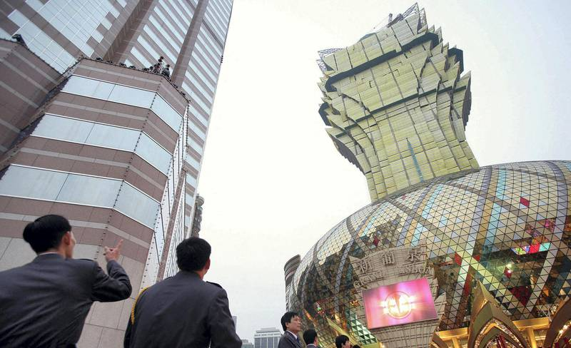 Visitors admire the new Grand Lisboa hotel and casino (R) ahead of the casino's official opening in Macau, 11 February 2007.  Billionaire tycoon Stanley Ho, who for 40 years held a monopoly on gambling in the southern Chinese territory and has seen his market share of the business slide with the opening since 2004 of rival Las Vegas-style casinos, launched his comeback campaign in Macau by opening a huge casino 11 February he hopes will bring punters back to his once-dominant gaming halls.     AFP PHOTO/Samantha SIN (Photo by SAMANTHA SIN / AFP)