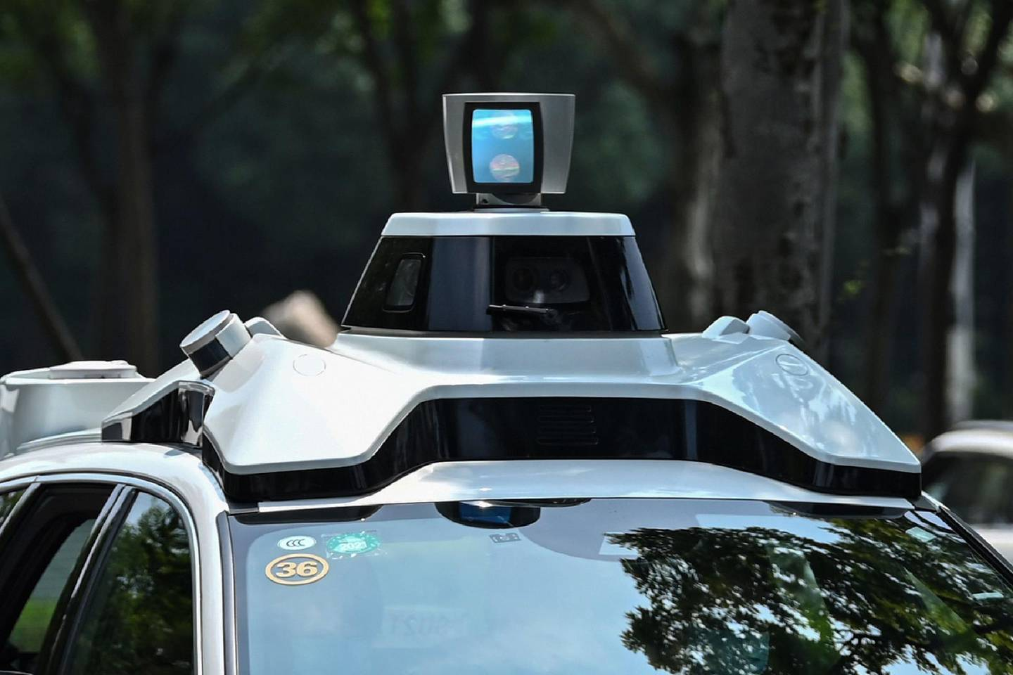 """This photo taken on July 22, 2020 shows a Didi Chuxing autonomous taxi during a pilot test drive on the streets in Shanghai. Chinese entrants in the race to put autonomous vehicles on the road are bringing """"robotaxis"""" online in hopes that a hired-car format can be the key to unlocking wide acceptance of the futuristic technology. - TO GO WITH AFP STORY IT-China-automobile-autonomous-computers,FOCUS by Beiyi Seow and Dan Martin  / AFP / Hector RETAMAL / TO GO WITH AFP STORY IT-China-automobile-autonomous-computers,FOCUS by Beiyi Seow and Dan Martin"""