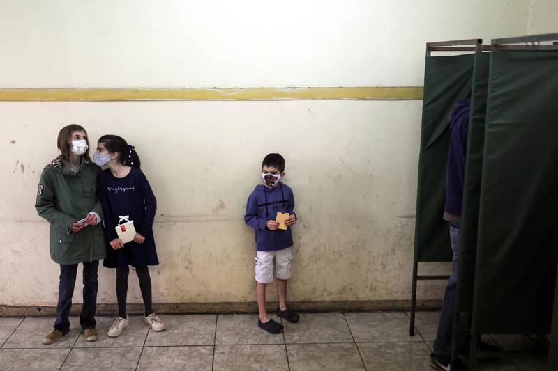 Children wait for their dad during the elections for governors, mayors, councillors and constitutional assembly members to draft a new constitution to replace Chile's charter, in Santiago, Chile May 15, 2021. REUTERS/Pablo Sanhueza