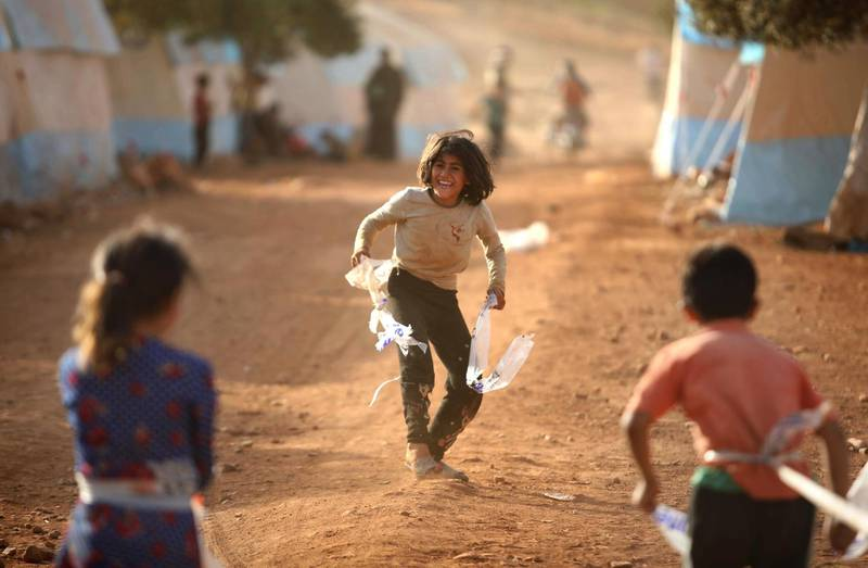 Displaced Syrian children play at a camp for internally displaced people near Kah, in the northern Idlib province near the border with Turkey on June 3, 2019 on the eve of Eid al-Fitr, which marks the end of the Muslim holy fasting month of Ramadan. The conflict in Syria has killed more than 370,000 people and displaced millions since it started in 2011. / AFP / Aaref WATAD