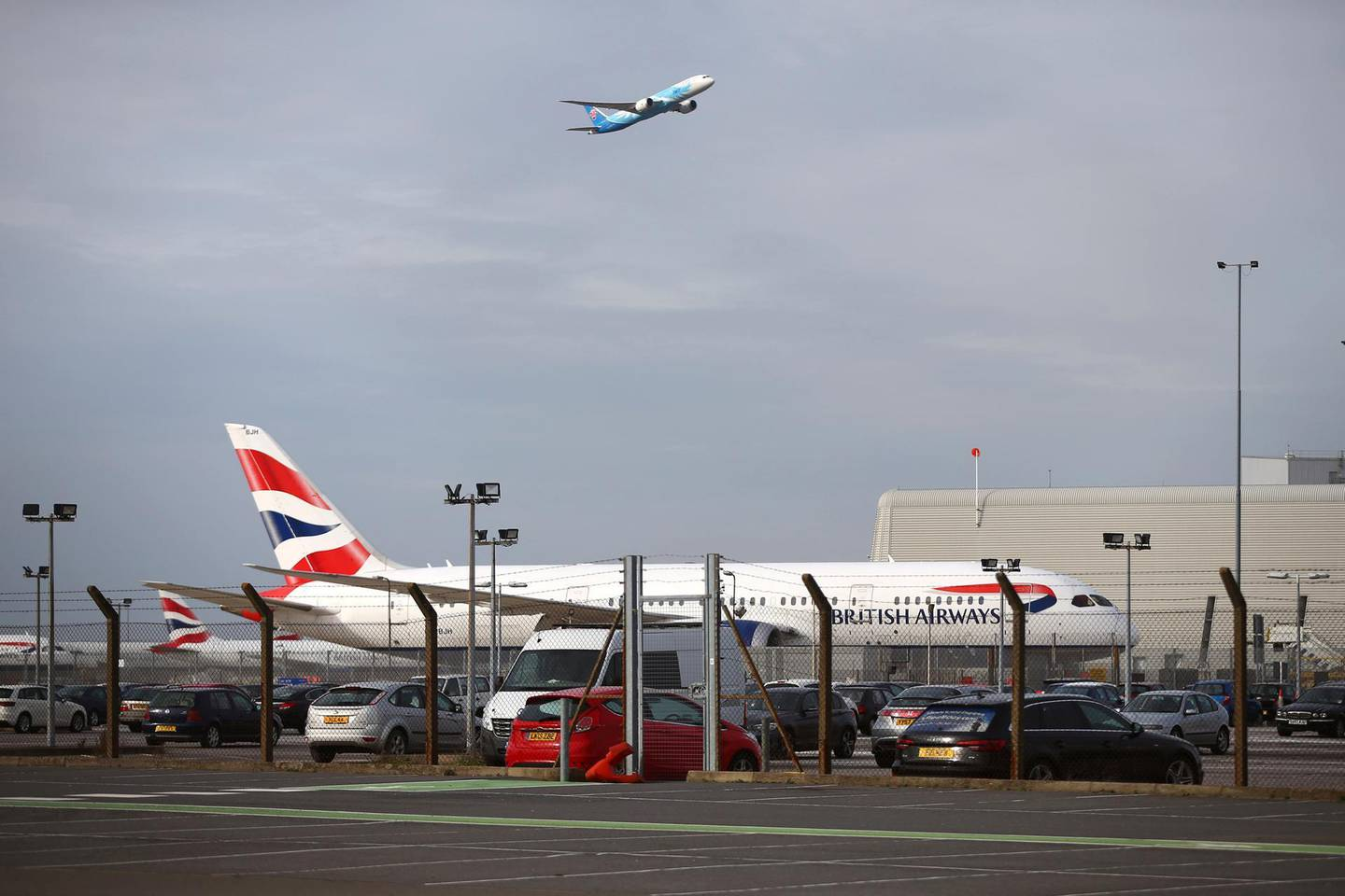 """LONDON, ENGLAND - FEBRUARY 13: A plane takes off in view of a British Airways aeroplane at Heathrow Airport on February 13, 2021 in London, England. From 15 February travellers to the UK from a country on the UK's travel ban """"red list"""" will be required to quarantine in a government-approved facility for ten days at their own cost. (Photo by Hollie Adams/Getty Images)"""