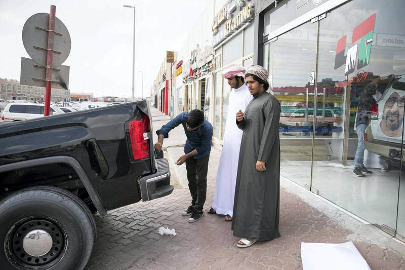 ABU DHABI, UNITED ARAB EMIRATES - NOVEMBER 27, 2018.   Obaid Al Mansoori, 17, right, and his friend Ahmed Al Marzooqi, 17, at Grand Plus Auto Accessories, are looking for National Day decorations for their car.  They have just returned from school, where they were presenting their gyr shaheen falcon in the classroom.   Car accessory shops in Mussafah are keeping busy as motorists rush to dress up their vehicles ahead of the UAE's 47th National Day.  (Photo by Reem Mohammed/The National)  Reporter:  HANEEN DAJANI Section:  NA